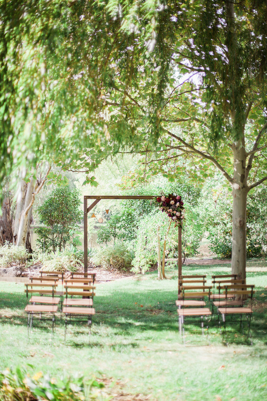 Ceremony styling featuring timber arch with timber bistro chairs.