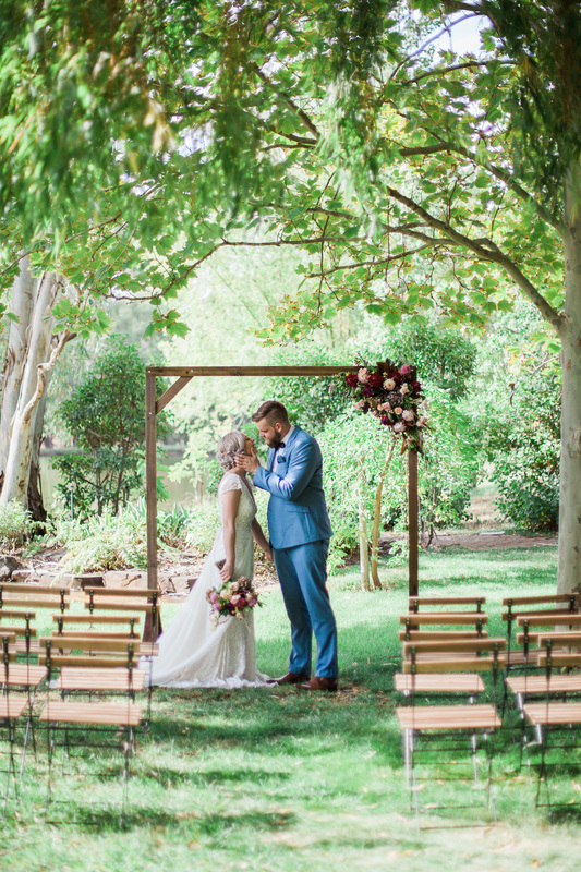Ceremony styling featuring timber arch with timber bistro chairs.Picture